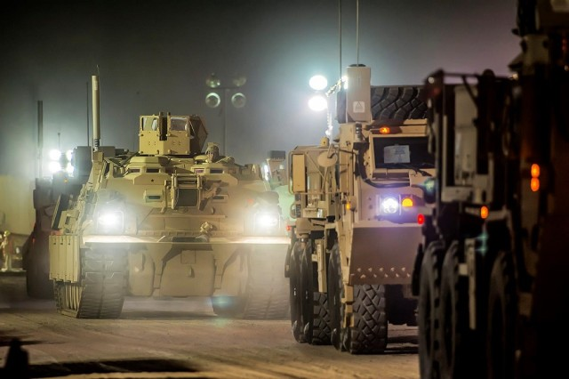 A convoy of vehicles drives through Army Prepositioned Stocks-5 remote staging lot in preparation for forward transport during a large-scale equipment issue from APS-5, at Camp Arifjan, Kuwait. APS-5 is managed and maintained by the 401st Army Field Support Brigade.