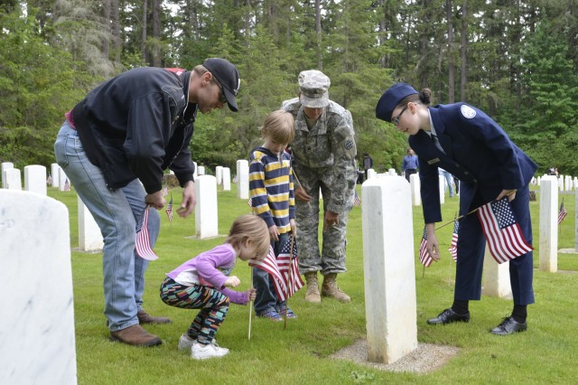 A child places a flag in front of a grave at the Camp Lewis Cemetery on JBLM Lewis Main during a past Memorial Day.