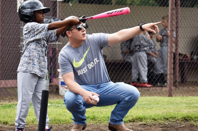 Steven Padgett, right, acting coach of the Camp Zama T-ball team, and Kaiden Pollard, a player, discuss batting during a game at Camp Zama May 18.