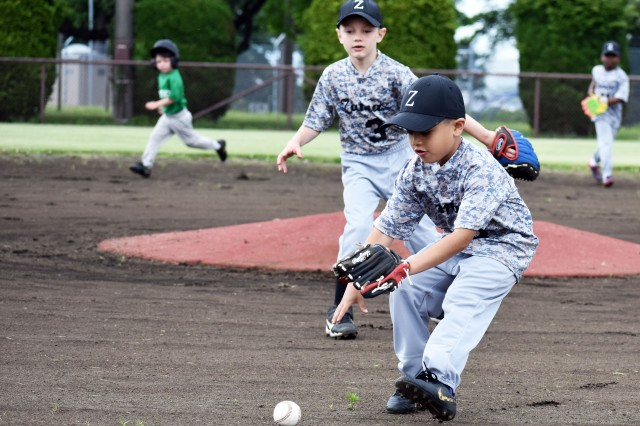 Nahum Giron, front, a player on the Camp Zama T-ball team, prepares to field a ball during a game at Camp Zama May 18. Carter Nelson, 6, stands ready to back him up.