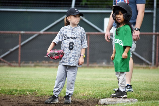 Elle Sprague, 6, a Camp Zama player, plays third base as Carly Uyeda, 5, a player on the Naval Air Facility Atsugi team, stands on base during a T-ball game at Camp Zama May 18.
