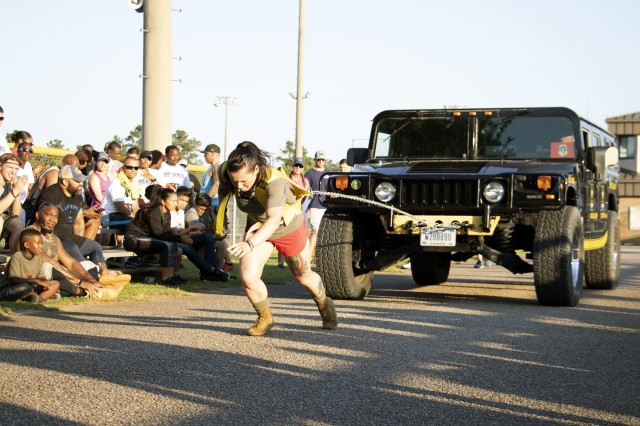"""Sgt. Samantha Escamilla, U.S. Army Dental Health Activity - Fort Jackson, tests her strength and endurance by pulling a 6,400 pound Hummer during the 2019 Fort Jackson Strongman/Strongwoman Competition May 16. Escamilla's 4-year-old daughter yelled """"get it"""" to encourage her mother during the competition. More than 30 competitors, along with their Families and friends, took over the Hilton Field Softball Complex to compete for top titles and prizes that included trophies, plaques and gift cards."""