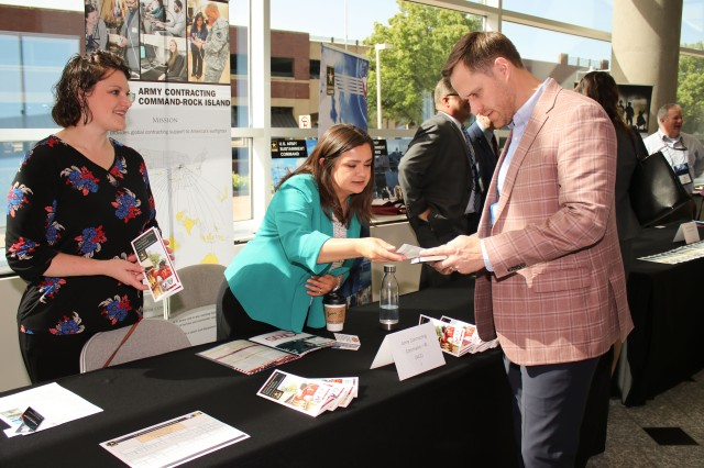 ACC-RI human resources specialists Emily Ruiz (left) and Amber Carter, answer questions about the center during NDIA's 12th Annual Midwest Government Contracting Symposium, held at the TaxSlayer Center, Moline, Ill., May 22-23. (Photo by Liz Glenn, ACC-RI Public Affairs)