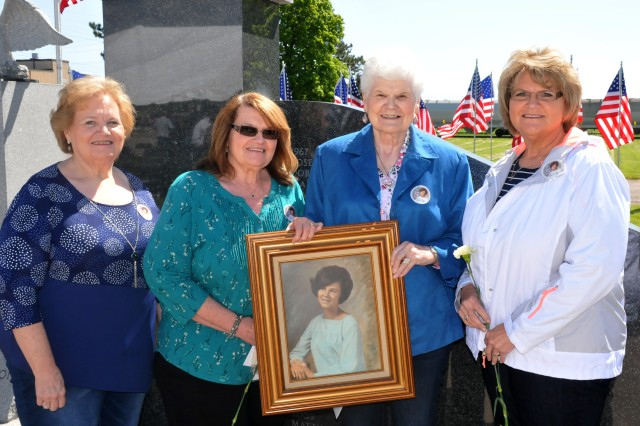 Sylvia Clark's siblings hold a framed pictured of their sister who passed away in October 1967 at the Iowa Army Ammunition Plant. Left to right are: LaVetta Smith, LaVerra Leebold, Rose Davidson and Sheryl Clark.