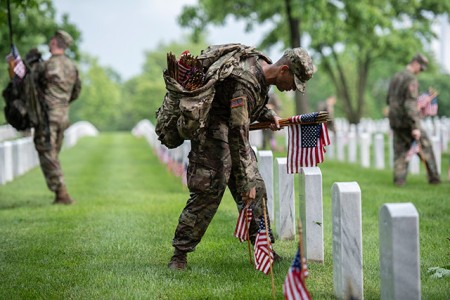 "Soldiers from the 3d U.S. Infantry Regiment (The Old Guard) place flags at headstones as part of ""Flags-In"" at Arlington National Cemetery, Va., May 23, 2019. For more than 55 years, Soldiers from the Old Guard have honored our nation's fallen heroes by placing flags at grave sites buried at both Arlington National Cemetery and the U.S. Soldiers' and Airmen's Home National Cemetery just prior to Memorial Day weekend. Within four hours, over 1,000 soldiers place 245,000 flags in front of every headstone and Columbarium and niche wall column."