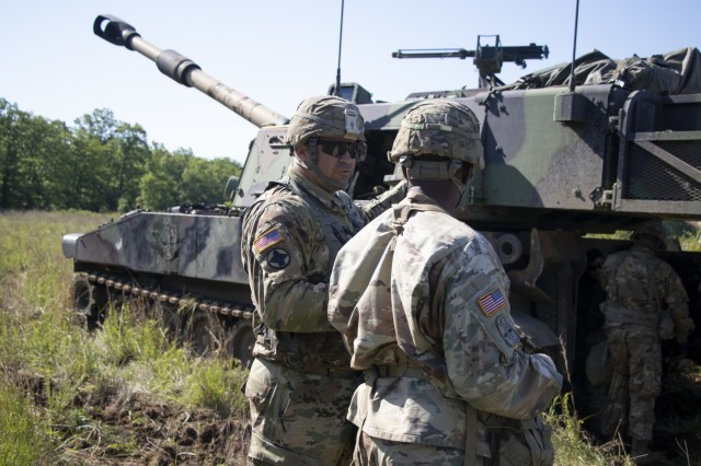 An Observer Coach/Trainer with the 2nd Battalion, 305th Field Artillery Regiment talks with a Soldier assigned to the 2nd Battalion, 142nd Field Artillery Brigade before M109 Paladin live fire training, May 17, 2019, at Camp Shelby, MS. (U.S. Army photo by Sgt. Roger Houghton)
