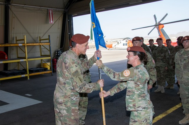 Maj. Amoreena York, Aviation Company (AVCO) commander, Task Force Sinai, passes the AVCO guidon to Col. Mark Ott, Task Force Sinai commander, symbolizing the relinquishment of command at South Camp, Egypt, May 23, 2019. AVCO supports rotary-wing aviation mission requirements for the Multinational Force & Observers (MFO). The MFO is headquartered in Rome, is an independent international organization, created by agreement between the Arab Republic of Egypt and the State of Israel, with peacekeeping responsibilities in the Sinai. (U.S. Army photo by, Staff Sgt. Kulani J. Lakanaria)