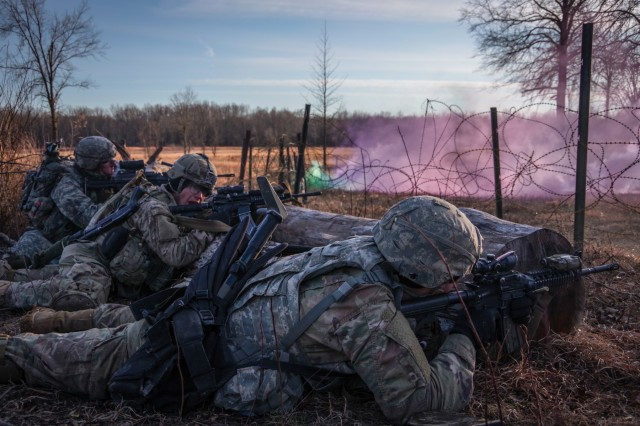 A paratrooper from the 1st Battalion, 508th Parachute Infantry Regiment, 3rd Brigade Combat Team, 82nd Airborne Division shouts orders while others engage a simulated enemy during a live-fire exercise Jan. 25 at Camp Atterbury, Indiana.  The platoon-level live-fire exercise tested the paratroopers' ability to conduct complex operations in challenging terrain and frigid temperatures against a simulated near-peer enemy.