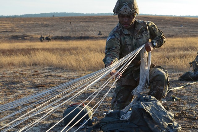 A paratrooper from the 3rd Brigade Combat Team, 82nd Airborne Division recovers his parachute on Bragg's Normandy Drop Zone after jumping from a U.S. Air Force C-17 Globemaster on February 1, 2019.  The paratroopers conducted a combat equipment static line airborne operation onto the drop zone to maintain their proficiency and rehearse their roles during follow-on missions.