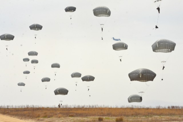 Paratroopers from Alpha Battery, 1st Battalion, 319th Airborne Field Artillery Regiment descend onto Fort Bragg's Normandy Drop zone after conducting a static-line airborne jump from an Air Force C-17 Wednesday, March 13th.  The Artillery paratroopers conducted the airborne operation to train for their hallmark mission of rapidly placing their artillery piece into operation and firing after conducting a static-line jump.
