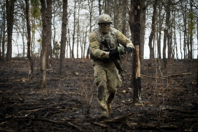 A paratrooper from Company B, 307th Airborne Engineer Battalion strings detonation cord away from a breaching charge during a company-level live fire exercise Tuesday, February 26 on Fort Bragg, North Carolina.