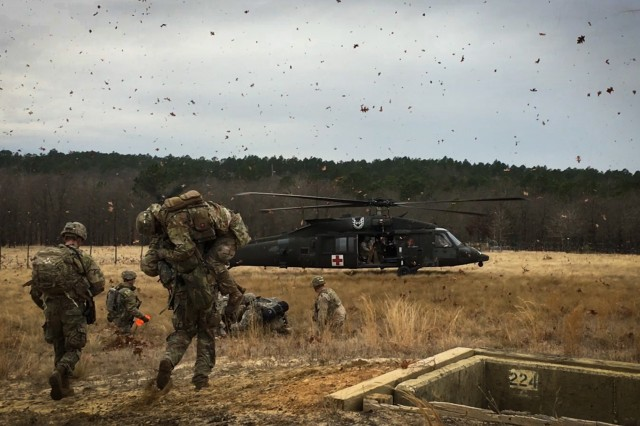 A paratrooper from 1st Battalion, 505th Parachute Infantry Regiment, 3rd Brigade Combat Team, 82nd Airborne Division carries a simulated casualty to a Medical Evacuation helicopter piloted by members of the 82nd Combat Aviation Brigade.