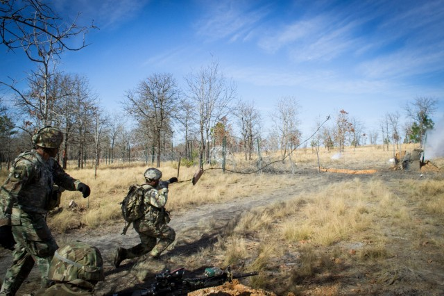 A paratrooper from Company C, 2nd Battalion, 505th Parachute Infantry Regiment, 3rd Brigade Combat Team, 82nd Airborne Division throws a grappling hook towards an obstacle to begin a breach during the Company's live-fire exercise conducted Sunday, February 24 on Fort Bragg, North Carolina.