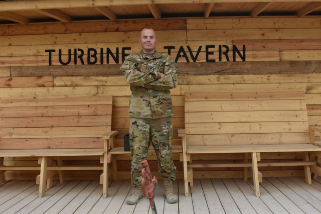 Task Force Apocalypse Soldier, Spc. Austin Zahara stands before the Turbine Tavern that he helped design and construct in Afghanistan.