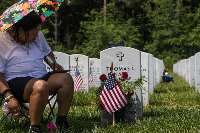 A family member places flowers on the grave of a loved one at Kentucky Veterans Cemetery-Central in Radcliff, Kentucky.