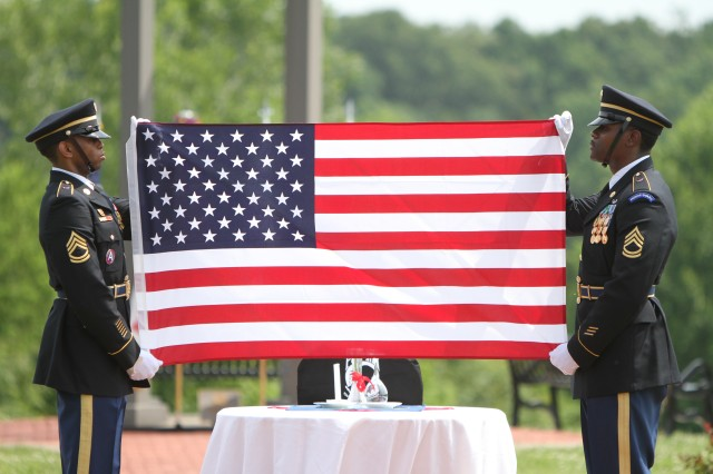 Two U.S. Army Human Resources Command Honor Guard Soldiers perform a ceremonial flag folding during the Memorial Day ceremony at Kentucky Veterans Cemetery-Central in Radcliff, Kentucky.