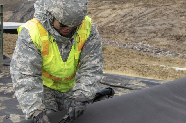 Alaska Army National Guard Pfc. Lamara Lainei, 207th Engineer Utility Detachment, cuts the geomat material that is laid down as a base layer at one of the sites of Resolute Castle in Cincu, Romania, May 11, 2019. Resolute Castle is a multi-national, joint exercise with real-world outputs of completed construction projects that build and enhance training capabilities around Eastern Europe.