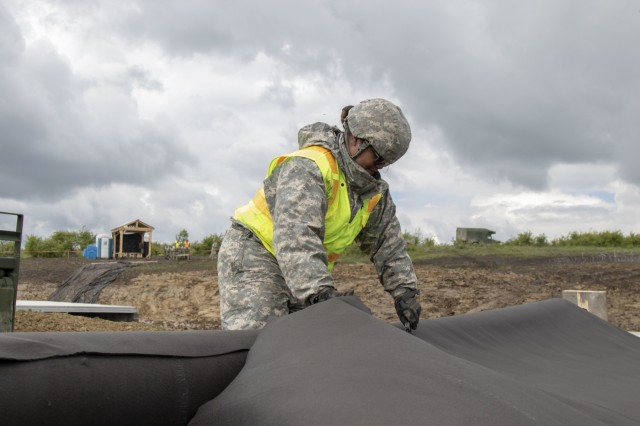 Alaska Army National Guard Pfc. Lamara Lainei, 207th Engineer Utility Detachment, cuts the geomat material that is layed down as a base layer at one of the sites of Resolute Castle in Cincu, Romania, May 11, 2019. Resolute Castle is a multi-national, joint exercise with real-world outputs of completed construction projects that build and enhance training capabilities around Eastern Europe.