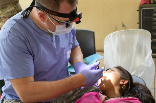 Capt. Eric Seaberg, a dentist assigned to the Missouri National Guard Medical Detachment, prepares a young girl for a tooth extraction by using a Novocain injection to block pain at a medical readiness training exercise during Beyond the Horizon, San Sebastian, Huehuetenango, Guatemala, May 21, 2019. The Guatemala Ministry of Public Health, U.S. Forces, Florida International University non-governmental organization, Guatemala Ministry of Social Services and Guatemalan forces provided medical, dental and pharmaceutical care to more than 3,700 San Sebastián, Huehuetenango, residents at the Beyond the Horizon 2019 medical readiness training exercise May 20-24, 2019. Beyond the Horizon is an annual exercise designed to build partner nation capacity for civil and military response to major disasters and the relationships built and sustained through this exercise demonstrate the ability of the U.S., and regional partners, to access and execute disaster relief activities throughout Central America.