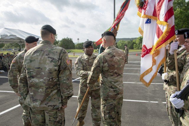 Incoming U.S. Army Operational Test Command Commander Col. Ronald R. Ragin passes the unit colors to OTC Command Sgt. Maj. William A. Justice, signifying the Change of Command is complete, and becoming OTC's 29th commander May 23.