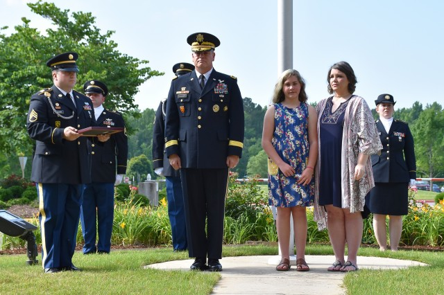 Lt. Gen. James H. Dickinson, commanding general, U.S. Army Space and Missile Defense Command/Army Forces Strategic Command, and members of the command honor Tiffany and Kylee Little, wife and daughter of Spc. Kyle Little, during the raising of a Gold Star Service Flag in recognition of Gold Star Families for Memorial Day Weekend. More than 50 Gold Star Family Members were present during raising of a Gold Star Flag with the American flag during a ceremony at the command's Redstone Arsenal, Alabama, headquarters May 24. (U.S. Army photo by Ronald Bailey)