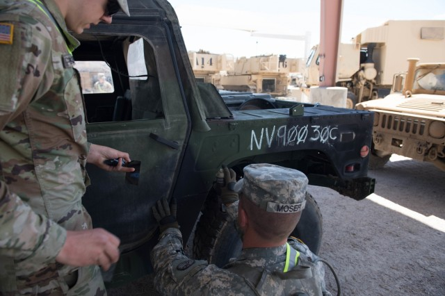 Nevada Army National Guard Pfc. Parker Badenhuizen and Cpl. Bryce Moser, Headquarters Headquarters Troop 1st Squadron, 221st Cavalry Regiment, 116th Cavalry Brigade Combat Team, install Velcro on an HMMWV to attach Multiple Integrated Laser Engagement System (MILES) May 25, 2019, at the National Training Center in Fort Irwin, Calif. The 116th CBCT is training at the NTC from 24 May to 20 June to prepare for its wartime missions.