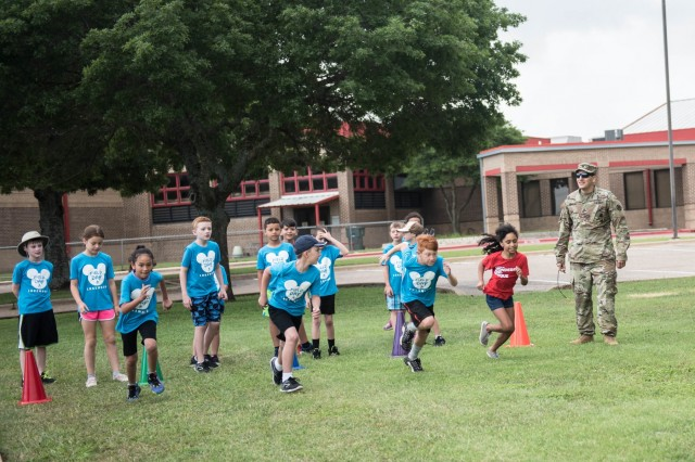 Lakewood Elementary School students begin Last Incredible Dash relay after Sgt. 1st Class Angel Munoz blows his whistle during Field Day May 24.  Field Day is an annual event for the school, and this year's event was Disney themed with each of the 19 stations and decorations centered around well-known Disney movies. (U.S. Army Photo by Sgt. 1st Class Kelvin Ringold)