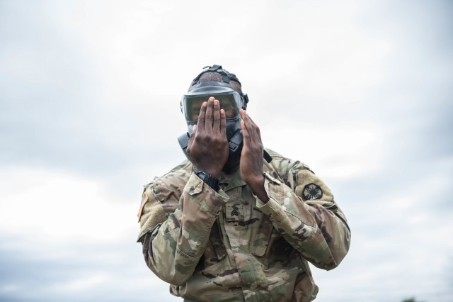 HHC, 13th ESC Sgt. Robert West checks the seal on this protective mask before being checked by his grader.  During the 13th ESC Best Warrior Competition May 20-23, Soldiers navigated CBRN lanes where there donned protective equipment and simulated decontaminating that same equipment. (U.S. Army Sgt. 1st Class Kelvin Ringold)