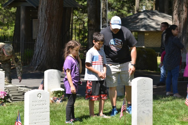 Retired Master Sgt. Dan Correll, right, and his children Matthew, 11, and Claire, 9, pause to read a tombstone at Camp Lewis Cemetery after attending Joint Base Lewis-McChord's Memorial Day ceremony May 27.