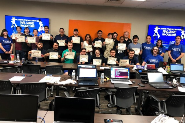 Hackathon finalists display their certificates of completion at the end of the full-day event.