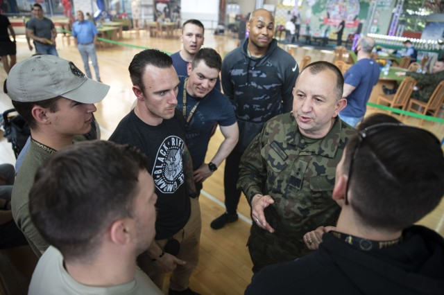 Polish Army Maj. Gen. Jaroslaw Roman Gromadzinski, talks with service members from 1st Armored Brigade Combat Team, 1st Infantry Division, during the 1st World Bench Press Championships of the Uniformed Services at Wroclaw, Poland, May 24 - 26, 2019. Eight service members, with 1st Armored Brigade Combat Team, 1st Infantry Division, competed as part of over 100 uniformed athletes at the international competition open to active and retired military service members and uniformed services. (U.S. Army photo by Sgt. Thomas Mort)