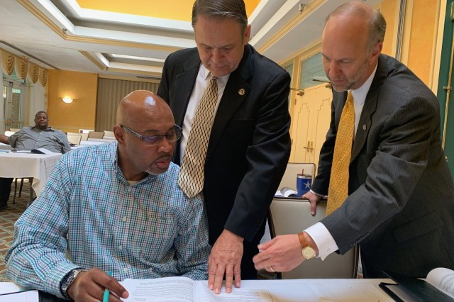 (Left) Bruce Walker listens while (center) Davis Tindoll, the director of Installation Management Command Sustainment, and (right) Glenn Wait, the JBM-HH chief of staff, explain federal resume writing during a break at the May 22 workforce development symposium.