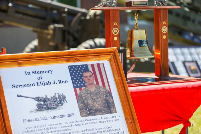The photo of U.S. Army Sgt. Elijah J. Rao, a field artillery metro crewmember assigned to 2nd Battalion, 77th Field Artillery Regiment, 2nd Infantry Brigade Combat Team, 4th Infantry Division, is placed in front off a bell, May 24, 2019, during a memorial ceremony on Fort Carson, Colorado. Rao was killed during an improvised explosive device attack in Afghanistan on Dec. 5, 2009. (U.S. Army photo by Staff Sgt. Neysa Canfield)