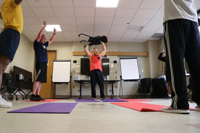 Dr. Aaron Edwards (center), a psychiatrist and medical director, goes the extra mile to inspire as he and Barry Greenwood, a marriage and family therapist in Madigan Army Medical Center's Residential Treatment Facility on Joint Base Lewis-McChord, Wash., lead a rigorous workout for patients on May 28.