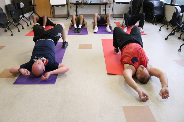 Dr. Aaron Edwards (right), a psychiatrist and medical director, and Barry Greenwood, a marriage and family therapist in Madigan Army Medical Center's Residential Treatment Facility on Joint Base Lewis-McChord, Wash., make sure the patients finish a rigorous workout strong on May 28.
