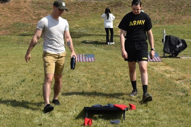 Pfc. Seth Watson (left) and Sgt. Timothy Cummings, USAG Humphreys HHC air traffic controllers, compete in a game of corn hole during the USAG--H Organization Day at Freedom Field, May 23. (U.S. Army photo by Sameria Zavala)
