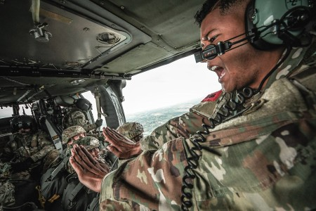 Jumpmaster gives 10-minute warning to paratroopers assigned to the 54th Brigade Engineer Battalion (Airborne). Soldiers  performed a series of airborne proficiency jumps from a CH-47 Chinook and two UH-60 Black Hawk helicopters in Aviano, Italy.