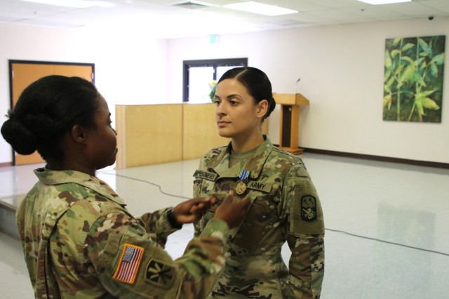 Capt. Jarietta Ross pins an Army Achievement Medal on the uniform of Spc. Marian Bermudeznieves on May 3, 2019 at Joint Base Pearl Harbor-Hickam, Hawaii. Spc. Bermudeznieves made commandants list while in BLC. (U.S. Army photo by Sgt. Malcolm Cohens-Ashley)