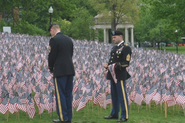 Command Sgt. Maj. Michael Pintagro places flags along Boston Common during the city's annual Massachusetts Military Heroes Fund ceremony.