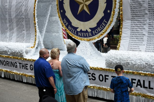 A Gold Star Family takes a moment in front of the Gold Star Family float following the City of Chicago Memorial Day parade, Mar. 25, 2019. Soldiers assigned to the 85th U.S. Army Reserve Support Command participated in parades and ceremonies, honoring fallen heroes, during Memorial Day weekend May 25-27, 2019. Brig. Gen. Kris Belanger, Commanding General, 85th USARSC and Cmd. Sgt. Maj. Theodore Dewitt, Command Sergeant Major, 85th USARSC, participated in a Gold Star Family Breakfast Saturday morning in Chicago to honor the sacrifice of fallen military heroes and then walked to Daley Plaza to participate in a wreath laying ceremony. Maj. Gen. Marion Garcia, Commanding General, 200th Military Police Command, spoke at the ceremony about a Soldier she had served with who died on active duty. Following the ceremony, military leaders walked to Lake and State Street for the Chicago Memorial Day parade and observed the parade from the reviewing stand. On Sunday, Belanger led ten new Army recruits in the oath of enlistment and delivered a speech at the Memorial Day observance in Norridge, Illinois. Later that day, Belanger and Dewitt finished the Memorial Day weekend by participating in the Arlington Heights Centennial Memorial Day parade. In North suburban Highland Park, Col. Daniel Jaquint, 85th USARSC, gave remarks at a Memorial Day service. (U.S. Army Reserve photo by Anthony L Taylor)