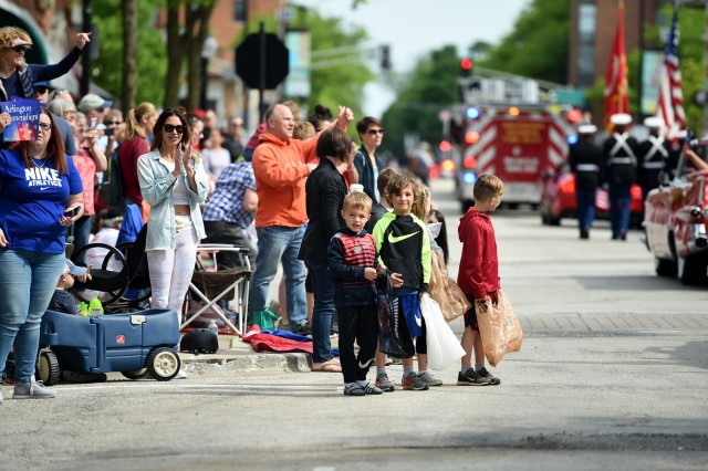Children look on during the Village of Arlington Heights Memorial Day parade, Mar. 27, 2019. Soldiers assigned to the 85th USARSC participated in parades and ceremonies, honoring fallen heroes, during Memorial Day weekend May 25-27, 2019. Brig. Gen. Kris Belanger, Commanding General, 85th USARSC and Command Sgt. Maj. Theodore Dewitt, Command Sergeant Major, 85th USARSC, participated in a Gold Star Family Breakfast Saturday morning in Chicago to honor the sacrifice of fallen military heroes and then walked to Daley Plaza to participate in a wreath laying ceremony. Maj. Gen. Marion Garcia, Commanding General, 200th Military Police Command, spoke at the ceremony about a Soldier she had served with who died on active duty. Following the ceremony, military leaders walked to Lake and State Street for the Chicago Memorial Day parade and observed the parade from the reviewing stand. On Sunday, Belanger led ten new Army recruits in the oath of enlistment and delivered a speech at the Memorial Day observance in Norridge, Illinois. Later that day, Belanger and Dewitt finished the Memorial Day weekend by participating in the Arlington Heights Centennial Memorial Day parade. In North suburban Highland Park, Col. Daniel Jaquint, 85th USARSC, gave remarks at a Memorial Day service. (U.S. Army Reserve photo by Anthony L Taylor)