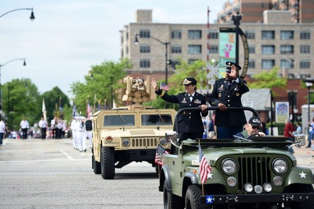 Brig. Gen. Kris Belanger, left, Commanding General, 85th U.S. Army Reserve Support Command, with Command Sgt. Maj. Theodore Dewitt, Command Sergeant Major, 85th USARSC, wave at a crowd during the Village of Arlington Heights Memorial Day parade, Mar. 27, 2019. Soldiers assigned to the 85th U.S. Army Reserve Support Command participated in parades and ceremonies, honoring fallen heroes, during Memorial Day weekend May 25-27, 2019. Belanger, and Dewitt, participated in a Gold Star Family Breakfast Saturday morning in Chicago to honor the sacrifice of fallen military heroes and then walked to Daley Plaza to participate in a wreath laying ceremony. Garcia, who was the Chicago parade Grand Marshal, shared a emotional story at the ceremony about a Soldier she had served with who died on active duty. Following the ceremony, military leaders walked to Lake and State Street for the Chicago Memorial Day parade and observed the parade from the reviewing stand. On Sunday, Belanger led ten new Army recruits in the oath of enlistment and delivered a speech at the Memorial Day observance in Norridge, Illinois. Later that day, Belanger and Dewitt finished the Memorial Day weekend by participating in the Arlington Heights Centennial Memorial Day parade. In North suburban Highland Park, Col. Daniel Jaquint, 85th USARSC, gave remarks at a Memorial Day service. (U.S. Army Reserve photo by Anthony L Taylor)