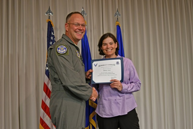 Air Force Lt. Gen. Jon Thomas, Air Mobility Command deputy commander, congratulates Bethany Himel, Military Surface Deployment and Distribution Command traffic management specialist, on her May 30 graduation from the Air Mobility Command Civilian Leadership Development Program at Scott Air Force Base, Illinois. (Photo by Alyssa Crockett)