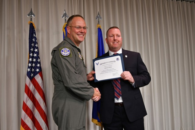 Air Force Lt. Gen. Jon Thomas, Air Mobility Command deputy commander, congratulates Anthony McKee, Military Surface Deployment and Distribution Command occupational safety and health manager, on his May 30 graduation from the Air Mobility Command Civilian Leadership Development Program at Scott Air Force Base, Illinois. (Photo by Alyssa Crockett)