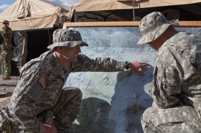 Idaho Army National Guard Sgt. Nathan Bundy reviews his unit's area of operations on a map with Spc. Cody Swift May 30, 2019, prior to the 2nd Battalion, 116th Cavalry Regiment's unit movement at the National Training Center in Fort Irwin, Calif. Bundy serves in the Idaho Army National Guard's 116th Cavalry Brigade Combat Team as a 35F intelligence analyst and teaches at Mountain Home High School in Mountain Home, Idaho.