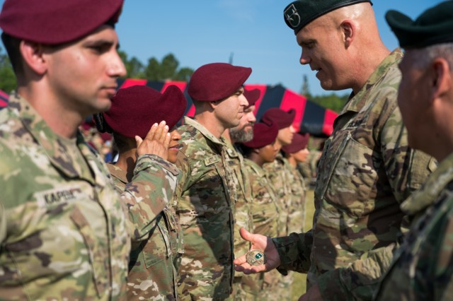 Maj. Gen. John Deedrick, 1st Special Forces Command (Airborne) commanding general, offers a coin to a newly-promoted Psychological Operations noncommissioned officer during a promotion ceremony larger than any other in Army Special Operations history, May 31, 2019. Following a review of the PSYOP rank structure, leaders identified a need for the PSYOP NCOs' rank to reflect their extensive training and education, and to correspond with the level of responsibility they assume downrange. Army and ARSOF leaders at multiple echelons worked for more than a year to achieve the grade plate change that would later create additional positions for the newly promoted staff sergeants and sergeants first class to be promoted into. Selected Soldiers - some who have waited more than 10 years for this day - have met the time in grade and service requirements for promotion, and have completed the appropriate level of professional military education.