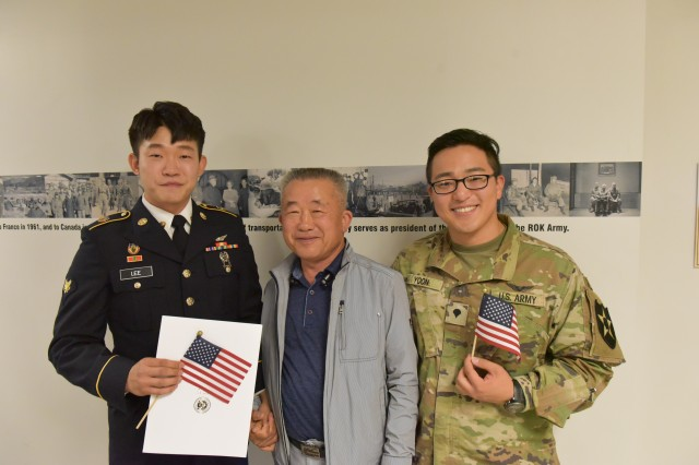(Left) Pfc. Namhum Lee, his father Lee Jong Ok, and Pfc. Seaokwon Yoon, poise after a naturalization ceremony at Camp Humphreys, May 22. Pfc. Lee received his U.S. citizenship certificate.