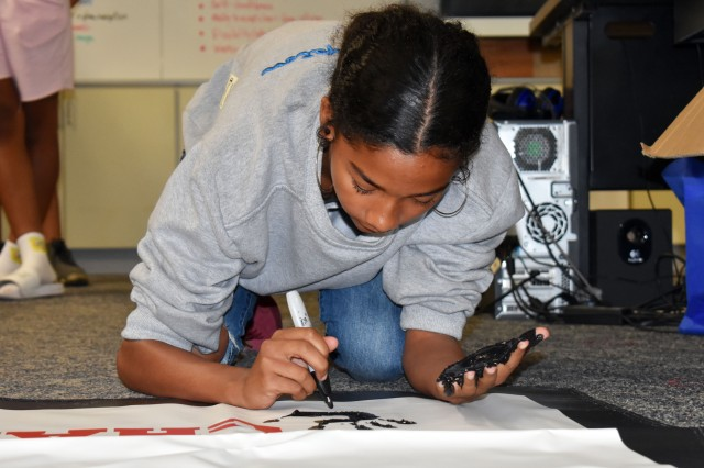 Kyleigh Rose, a player on the Zama Middle High School girls' soccer team, signs the team's championship banner at the school June 1. The team won the Department of Defense Education Activity-Pacific Girls' Soccer Division II championship at Misawa Air Base, Japan, May 24.