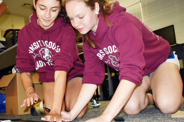 Meridean Duarte, left, and Siobhan Grabski find a good spot to put Duarte's handprint on the team's championship banner at the school June 1. The team won the Department of Defense Education Activity-Pacific Girls' Soccer Division II championship at Misawa Air Base, Japan, May 24.