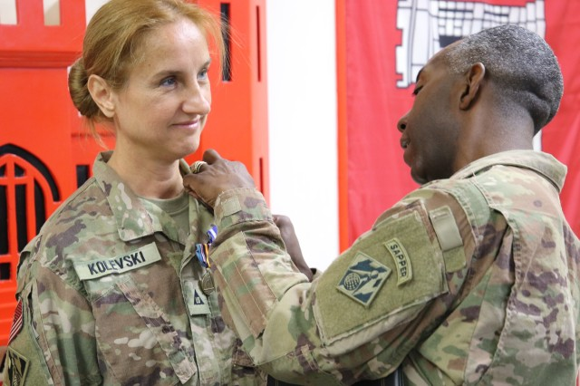 Col. Jason E. Kelly pins on the third of three medals awarded to Emilija Kolevski as she ends her deployment in support of the Afghanistan USACE District.